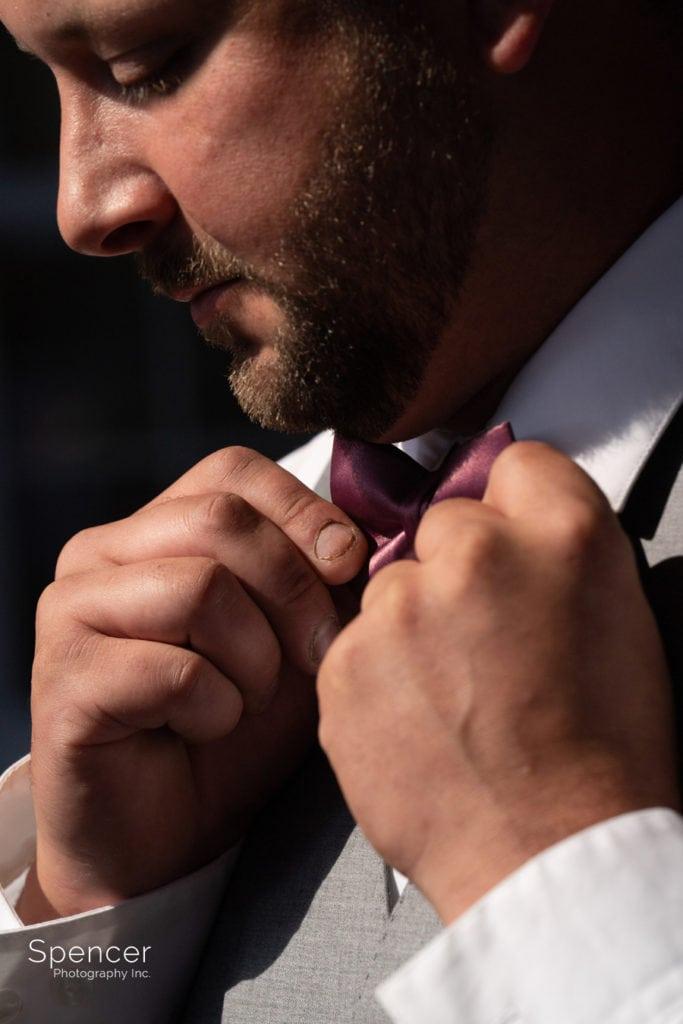 portrait of groom fixing tie