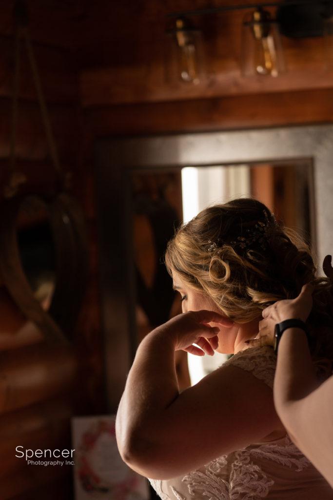 bride putting on wedding dress at Parker Barn