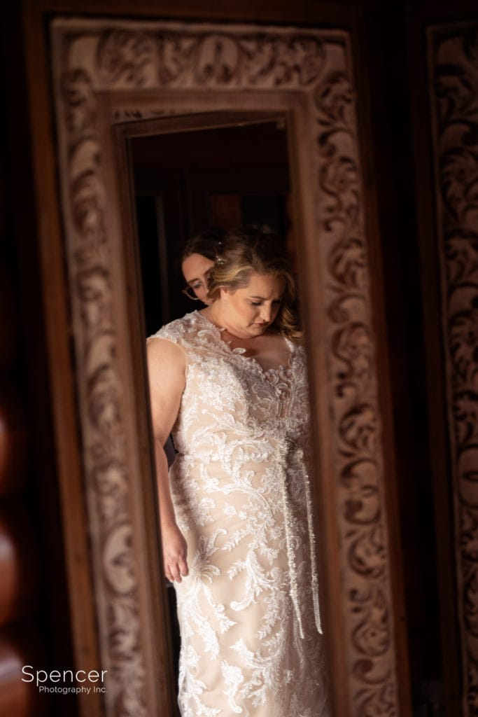 reflection of bride putting on wedding dress at Parker Barn