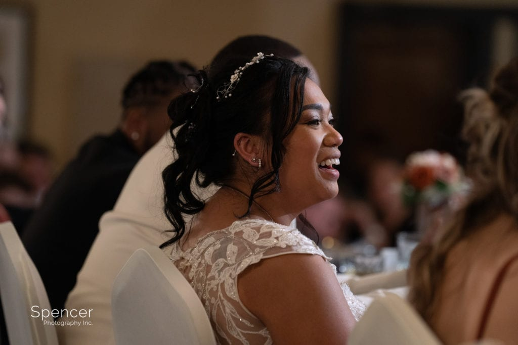 bride smiling during maid of honor speech