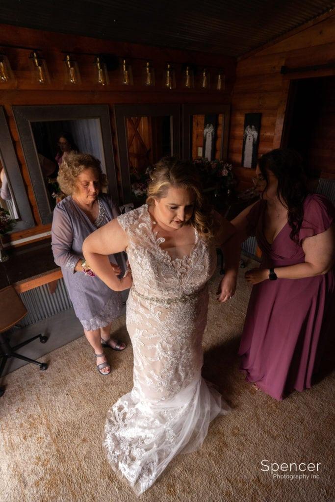 bride getting into wedding dress at Parker Barn