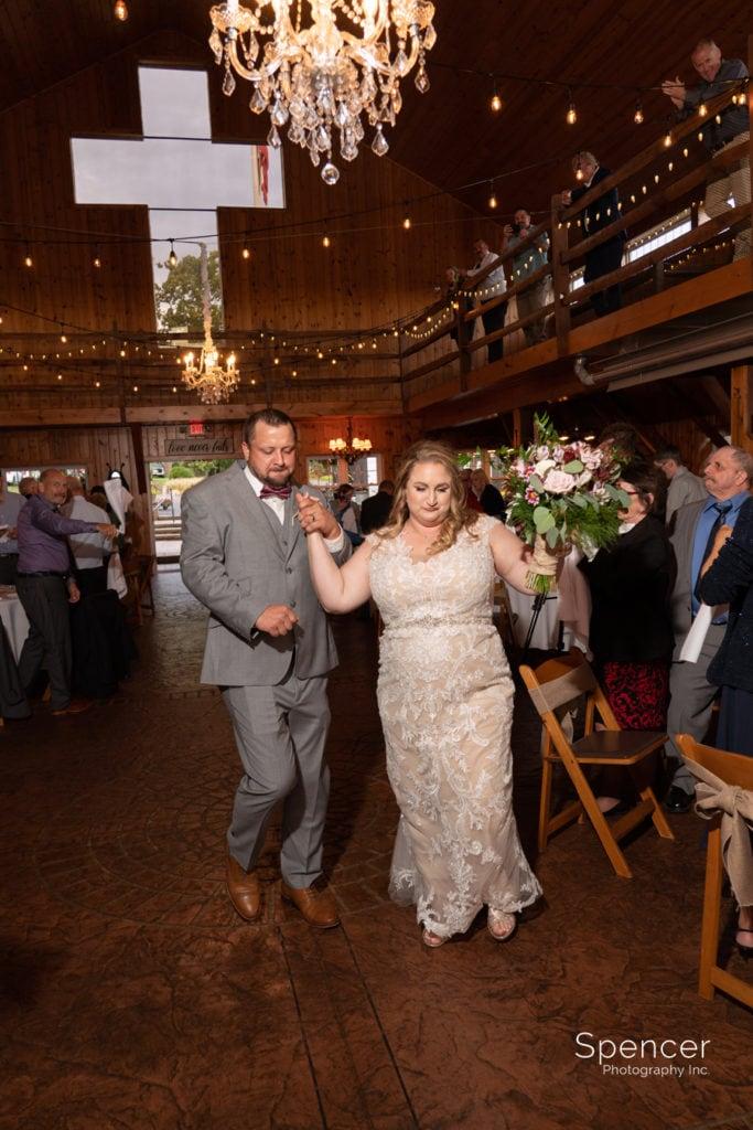 bride and groom entering wedding reception at Parker Barn