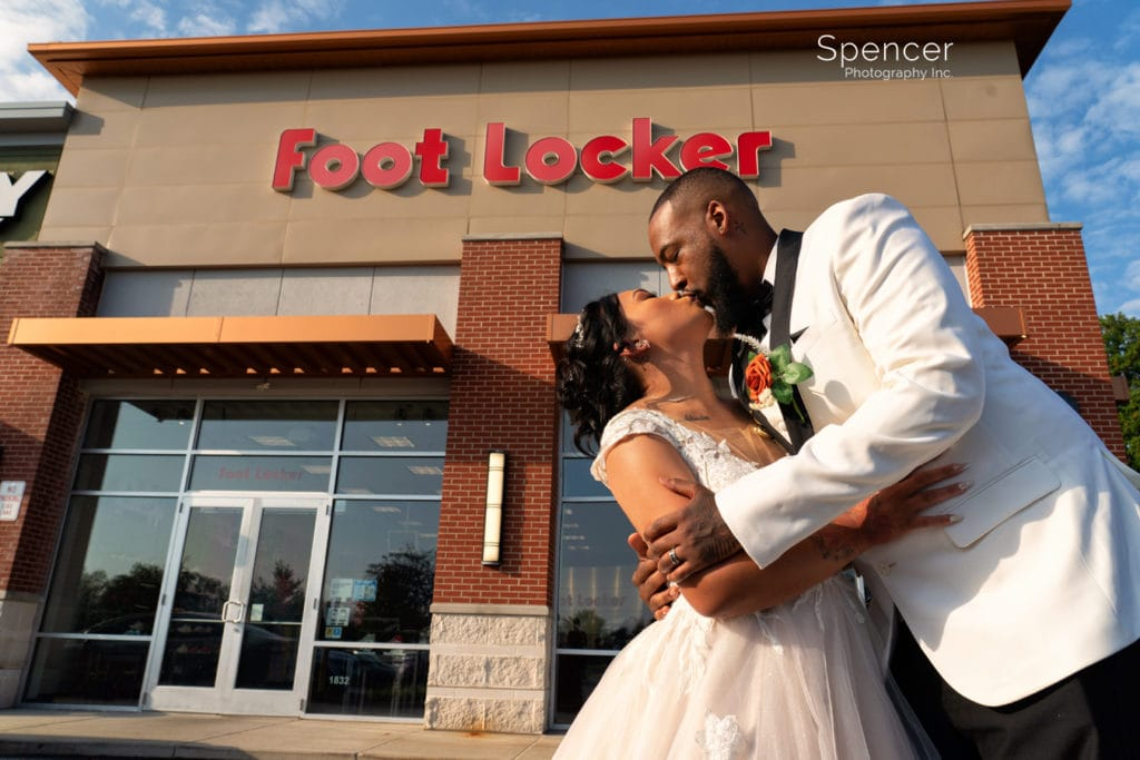 bride and groom kissing in front of Cleveland Foot Locker