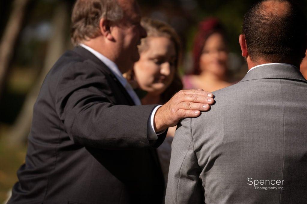 comforting groom at wedding ceremony