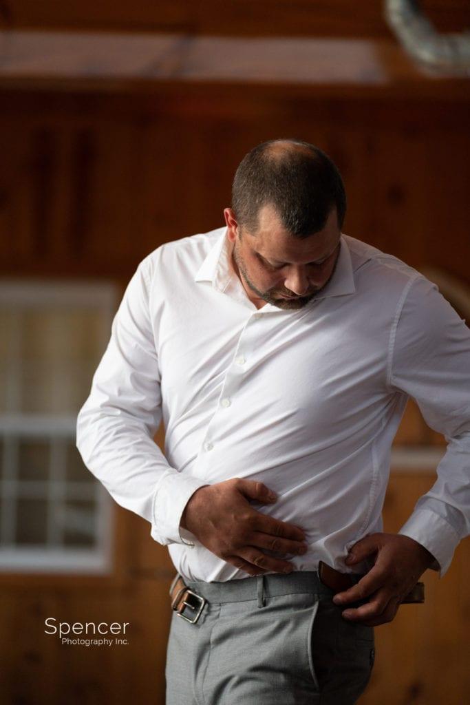 groom putting on belt at Parker Barn