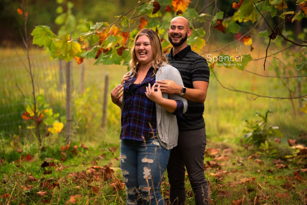 couple laughing during engagement session at mill stream park